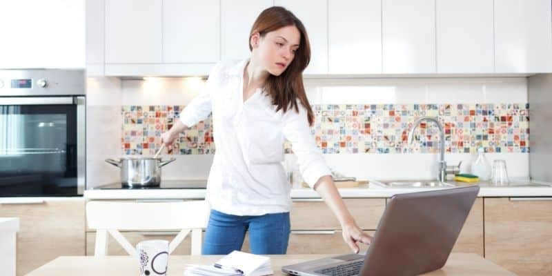 Busy mom multitasking cooking while working on laptop