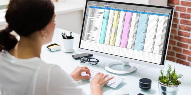 working mom using spreadsheet on computer to track income